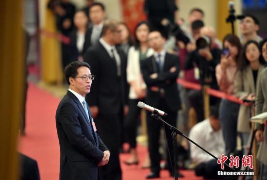 """3月8日,十三届全国人大二次会议在北京人民大会堂举行第二次全体会议。图为国务院港澳事务办公室主任张晓明在""""部长通道""""接受采访。中新社记者 侯宇 摄"""