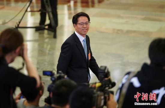 """3月8日,十三届全国人大二次会议在北京人民大会堂举行第二次全体会议。图为国务院港澳事务办公室主任张晓明步入""""部长通道""""接受采访。中新社记者 崔楠 摄"""