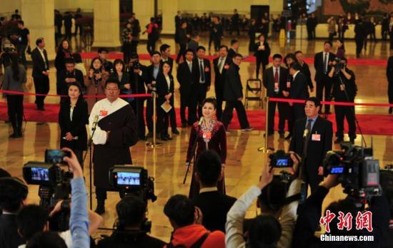 """3月9日,全国政协十三届二次会议在北京人民大会堂举行第二次全体会议。图为全国政协委员扎西(左)、迪丽娜尔·阿布拉(中)、廷·巴特尔(右)在""""委员通道""""接受采访。中新社记者 于海洋 摄"""