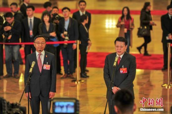 """3月9日,全国政协十三届二次会议在北京人民大会堂举行第二次全体会议。图为全国政协委员赵家军(右)、吕红兵(左)在""""委员通道""""接受采访。记者 于海洋 摄"""