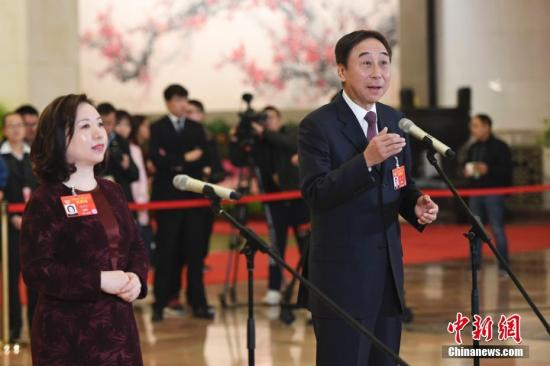 """3月9日,全国政协十三届二次会议在北京人民大会堂举行第二次全体会议。图为全国政协委员刘月宁(左)、冯巩(右)在""""委员通道""""接受采访。记者 张娅子 摄"""