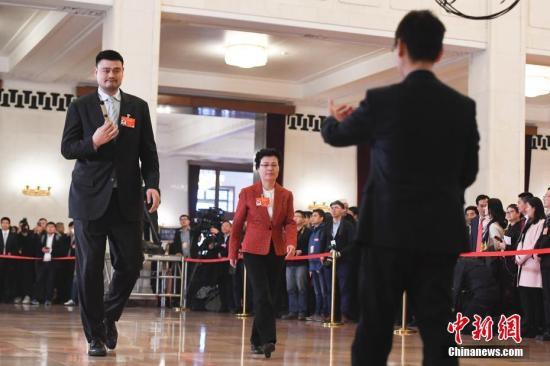 """3月9日,全国政协十三届二次会议在北京人民大会堂举行第二次全体会议。图为全国政协委员王艳霞(中)、姚明(左)在""""委员通道""""接受采访。中新社记者 张娅子 摄"""