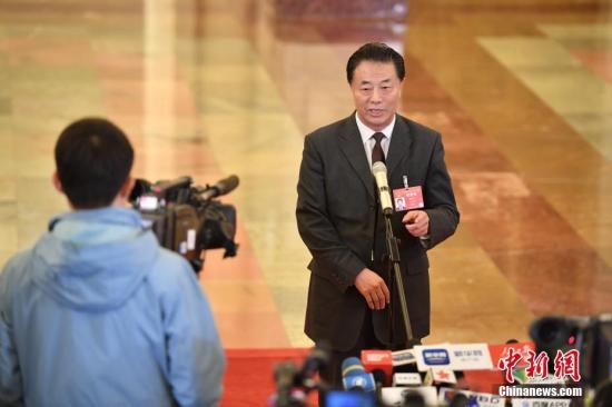 """3月12日,十三届全国人大二次会议在北京人民大会堂举行第三次全体会议。图为水利部部长鄂竟平在""""部长通道""""接受采访。<a target='_blank' href='http://www.chinanews.com/'>中新社</a>记者 侯宇 摄"""