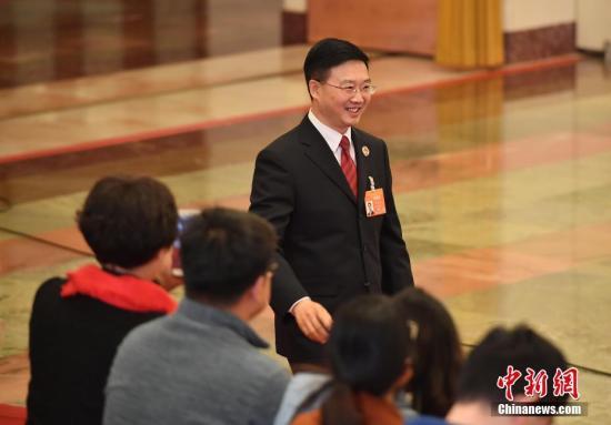 """3月12日,十三届全国人大二次会议在北京人民大会堂举行第三次全体会议。图为最高人民检察院副检察长童建明步入""""部长通道""""接受采访。中新社记者 侯宇 摄"""