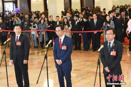 """3月13日,全国政协十三届二次会议在北京人民大会堂举行闭幕会。图为全国政协委员陈卓禧(右)、梁华(中)、骆沙鸣(左)在""""委员通道""""接受采访。中新社记者 张娅子 摄"""