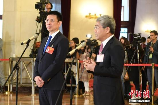 """3月13日,全国政协十三届二次会议在北京人民大会堂举行闭幕会。图为全国政协委员白重恩(右)、黄立(左)在""""委员通道""""接受采访。中新社记者 张娅子 摄"""