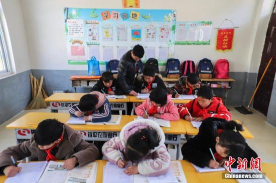 资料图:老师在教室里给小学生们辅导作业。中新社记者 王中举 摄