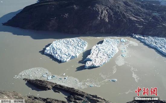 近日,智利巴塔哥尼亚的格雷冰川发生断裂,两座冰山从冰川上脱落后漂浮在湖中。
