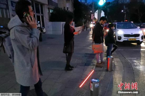 """本地工夫3月12日,以色列特推维妇内地地域街讲呈现了一批装置正在的LED交通讯号灯。那些旌旗灯号灯是专走路湾机的""""垂头族""""筹办的,用以避免发作交通不测。"""