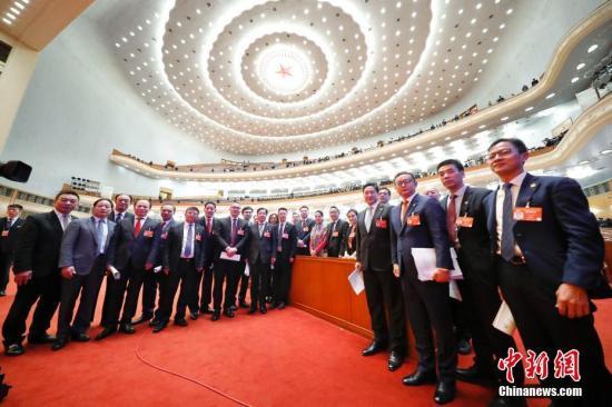 3月13日,中国人民政治协商会议第十三届全国委员会第二次会议在北京人民大会堂举行闭幕会。图为受邀列席会议的海外侨胞在闭幕会后合影留念。中新社记者 刘震 摄