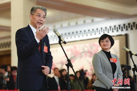 """3月13日,全国政协十三届二次会议在北京人民大会堂举行闭幕会。图为全国政协委员梁琰(右)、李晓鹏(左)在""""委员通道""""接受采访。中新社记者 张娅子 摄"""