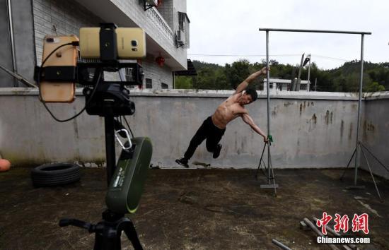 资料图:农村小伙黄海木正在通过手机直播其健身锻炼,变成网红肌肉达人张斌 摄