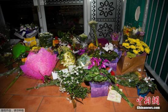 材料图:公众正在新西兰都城惠灵顿的浑实寺前台阶上摆放陈花战烛炬悲悼枪击案罹难者。