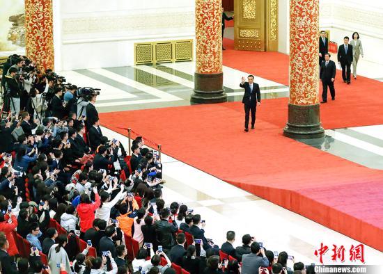 3月15日,十三届全国人大二次会议闭幕后,中国国务院总理李克强在北京人民大会堂金色大厅会见采访十三届全国人大二次会议的中外记者并回答记者提出的问题。图为李克强步入会场,并向记者挥手致意。<a target='_blank' href='http://www.chinanews.com/'>中新社</a>记者 刘震 摄