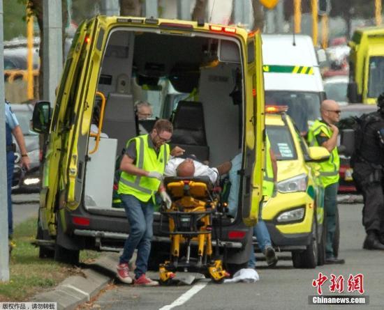 图为一名受伤人员被送入救护车。