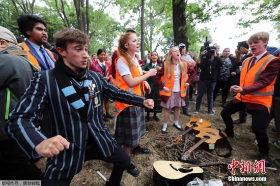 """资料图:当地时间3月18日,新西兰克莱斯特彻奇市,清真寺枪击案发生后第三天,民众在校园及清真寺附近举行集会,燃烛、献花悼念遇难者。为表达哀悼,一些学生还用毛利人传统战舞""""哈卡舞""""(Haka)向遇难者致敬。"""