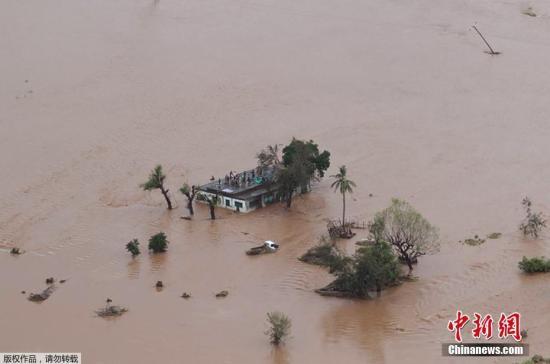 """近日,强热带气旋""""伊代""""登陆莫桑比克中部地区,索法拉省贝拉市交通、供电和通讯中断。据贝拉市当地红十字会和相关机构3月18日表示,此次飓风造成莫桑比克和津巴布韦至少162人死亡,多人失踪,并在莫桑比克城市贝拉造成""""大规模和恐怖""""的破坏。图为受灾民众在房顶上等待救援。"""