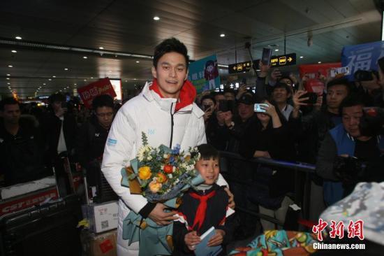 """资料图:孙杨抵达青岛备战全国游泳冠军赛,在机场与小""""粉丝""""互动。 胡耀杰 摄"""