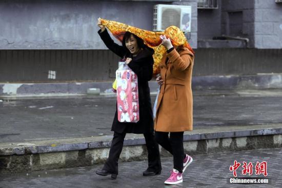 3月20日下午,北京迎来降雨,气温下降。北京市气象台19日发布了今年来首个寒潮预警,预计3月20至21日北京地区将出现寒潮天气,最低气温将下降8至10℃。图为民众在雨中出行。中新社记者 贾天勇 摄