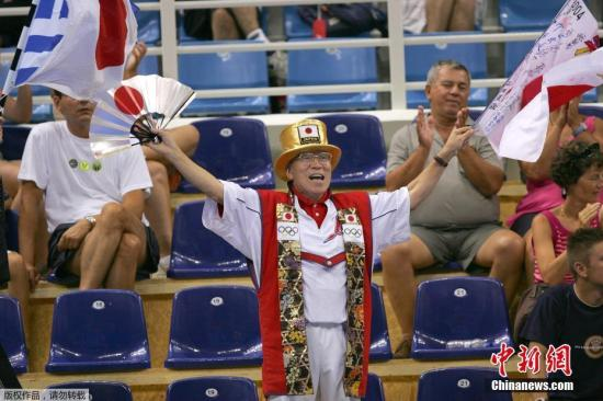 图为2004年悉尼奥运会兵乓球比赛现场山田直稔为日本球员振臂高呼。