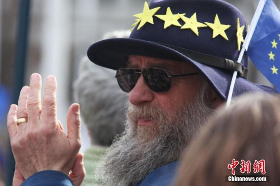 """3月23日,在欧盟同意英国延迟脱欧、英国脱欧前景仍面临""""灾难的不确定性""""困境之际,伦敦市中心举行了大规模呼吁举行""""第二次脱欧公投""""的示威游行。名为""""交给人民""""的组织者声称,参加示威游行的英国民众来自全国各地,超过一百万人。图为一满头是欧盟标志的老人为演讲者鼓掌。/p中新社记者 张平 摄"""