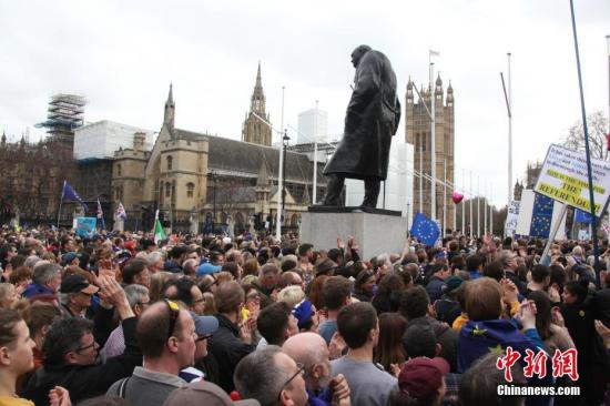 """3月23日,在欧盟同意英国延迟脱欧、英国脱欧前景仍面临""""灾难的不确定性""""困境之际,伦敦市中心举行了大规模呼吁举行""""第二次脱欧公投""""的示威游行。名为""""交给人民""""的组织者声称,参加示威游行的英国民众来自全国各地,超过一百万人。图为人群聚集在市中心议会广场,在英国历史上杰出政治人物丘吉尔塑像下,期盼获得掌握未来命运的权利。<a target='_blank' href='http://www.chinanews.com/'>中新社</a>记者 张平 摄"""