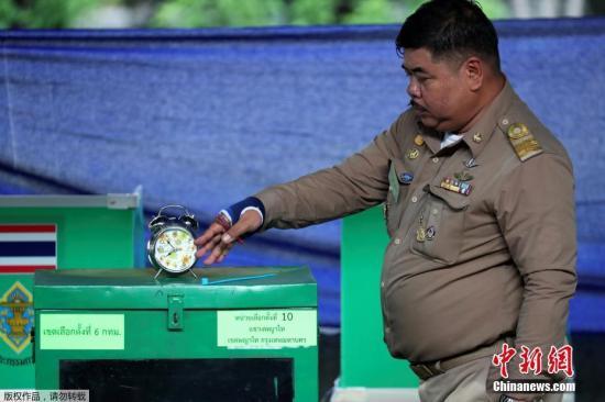 """在本次选举中,约有700万名""""首投族""""。有分析称,他们的投票取向足以左右大局。另外,泰国超过一半的选民属于低收入者及农民,他们也成为各政党拉票的对象。图为投票开始前泰国警察在投票箱前核对时钟设置的时间。"""