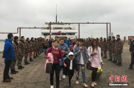 """3月24号上午,在广西北海涠洲岛搁浅了十多个小时的""""北游25""""游轮终于靠港,700多名旅客得以安全上岸,登上了涠洲岛。余娜 摄"""