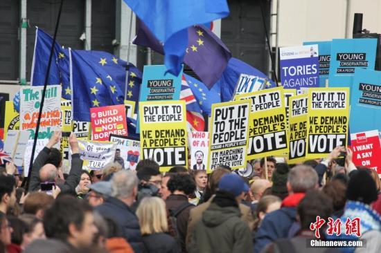 """3月23日,在欧盟同意英国延迟脱欧、英国脱欧前景仍面临""""灾难的不确定性""""困境之际,伦敦市中心举行了大规模呼吁举行""""第二次脱欧公投""""的示威游行。名为""""交给人民""""的组织者声称,参加示威游行的英国民众来自全国各地,超过一百万人。图为示威游行队伍中,标语牌林立,欧盟旗迎风招展。<a target='_blank' href='http://alien1111.com/'>中新社</a>记者 张平 摄"""
