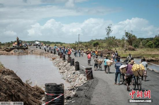 """强热带气旋""""伊代""""14日晚间从贝拉登陆莫桑比克,带来暴风、强降雨天气和洪涝灾害,影响索法拉、马尼卡、太特和赞比西亚等省份。图为当地民众在重新修复的N6公路上行走。文字来源:新华网"""