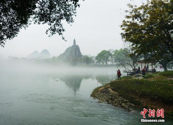 """资料图为:3月28日,平流雾中的桂林老八景""""塔山""""。唐梦宪 摄"""
