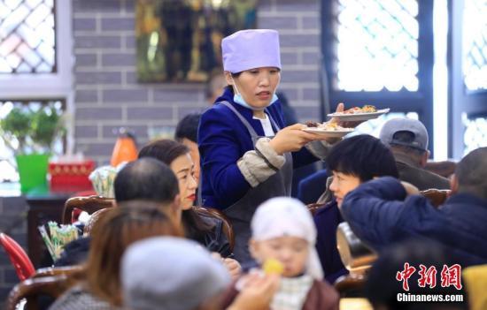 宁夏吴忠杨德福早茶拉面店的服务员为顾客端菜。中新社记者 杜洋 摄