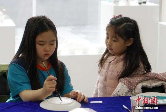 图为在现场进行的山东海洋贝瓷文化展上,小伴侣体验瓷器艺术创作。中新网记者 曾鼐 摄