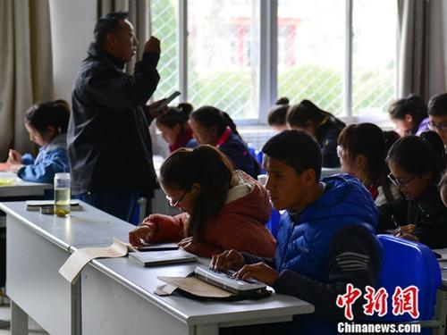 4月2日,次仁(前右一)在课上用盲文点显器记录老师所讲的内容。中新社记者 江飞波 摄