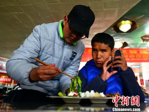 4月2日,次仁的同学普扎西帮忙将饭菜汇集到一起,以方便次仁食用。中新社记者 江飞波 摄