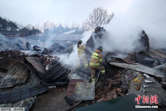 资料图:当地时间4月5日,韩国森林大火火光冲天。图为消防人员扑灭局部大火。