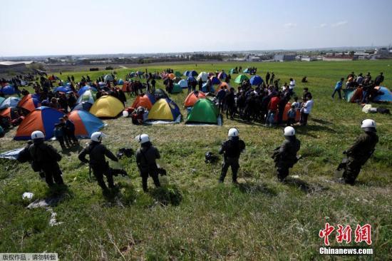 資料圖:希臘北部城市迪亞瓦塔的郊外,防暴警察在難民搭建的營地旁站崗。