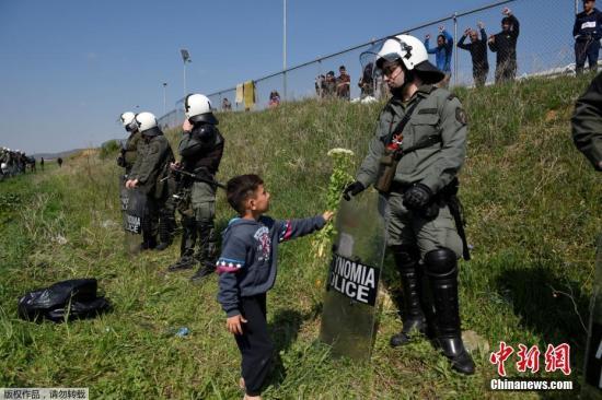 当地时间4月4日,希腊北部城市迪亚瓦塔的野外,防暴警察在难民搭建的营地旁站岗,别名来自难民家庭的幼孩向他送去一束鲜花。