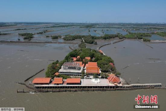 """4月9日据香港《文汇报》报道,泰国中部一间寺庙原本位于泰国湾岸边,但随着气候变化令海平面上升,以及城市发展加剧海岸水土流失,寺庙现已变成在孤岛上,被称为""""漂浮寺庙""""。"""