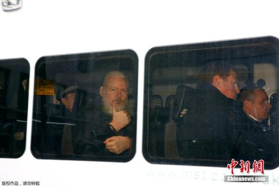 """据外媒4月11日报道,英国警方逮捕了维基解密创始人阿桑奇。据此前媒体报道,阿桑奇自2012年起一直藏身在厄瓜多尔驻伦敦大使馆。由于担心在维基解密的活动被瑞典政府引渡给美国,他请求政治庇护。2018年12月,厄瓜多尔总统莫雷诺曾表示,已收到英国的书面保证,称阿桑奇不会被引渡到可能导致其生命危险的国家。他可以离开该国驻伦敦大使馆,相关的安全顾虑""""已被清除""""。但阿桑奇对英厄之间达成的协议表示拒绝,因为它没有保证阿桑奇不会被引渡到美国。图为维基解密创始人阿桑奇在警车内向媒体竖拇指。"""