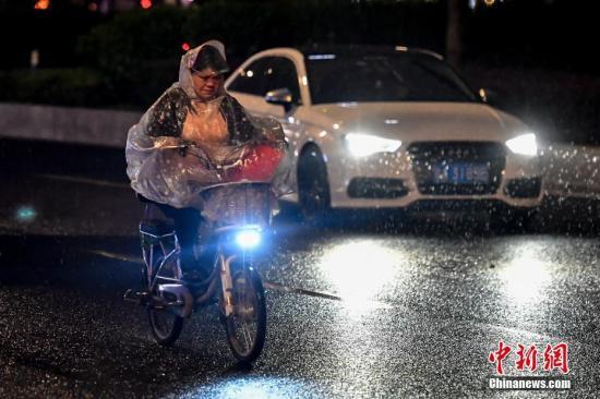 4月11日晚,一名女子驾驶电动车行驶在雨中。当晚,广州市区出现强降水和雷雨大风等强对流天气。<a target='_blank' href='http://www.ricasputas.com/'>中新社</a>记者 陈骥旻 摄