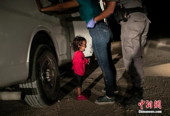 资料图:2019荷赛奖年度图片:美墨边境哭泣的小女孩  John Moore(Getty Images) 摄  当地时间2018年6月12日,美国得克萨斯州麦卡伦,美墨边境上,,洪都拉斯移民Sandra Sanchez被边防警拦下搜身,她的女儿Yana站在一?#21592;?#21523;哭。