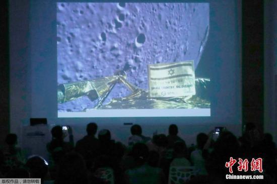 """資料圖:當地時間4月11日,SpaceIL和以色列航空工業公司(IAI)發布了一張""""創世紀""""號航天器在月球登陸過程中拍攝的月球照片。據報道,""""創世紀""""號在登陸月球的最后時刻,發生故障并墜落在月球表面。據悉,""""創世紀""""號航天器原計劃是在月球上實現軟著陸。圖為人們在以色列""""Planetaya天文館""""觀看""""創世紀""""號拍攝的月球照片。"""