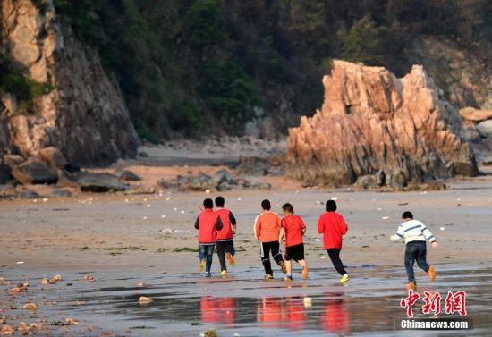 """福建省霞浦县下浒镇是一个靠海的乡镇,美丽的沙滩吸引了许多游客前来观光。33岁的陈龙强是当地的一个瓷砖店老板,从小就喜欢踢球的他在2016年组建了一只""""长风足球队"""",队员主要是当地小学的学生。对于""""长风足球队""""的孩子们来说,快乐并不复杂。一片沙滩,用树枝画成的边线,用装修水管组装的球门,一个""""百元足球场""""就此诞生。但随着一声哨响,足球滚动,孩子们的欢声笑语却盖过了海涛的轰鸣。图为4月9日,队员在海边跑步训练。<a target='_blank' href='http://www.chinanews.com/'>中新社</a>记者 王东明 摄"""