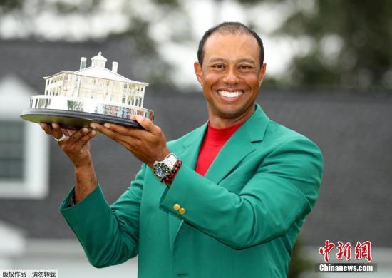 """身穿冠军象征""""绿夹克""""的伍兹举起大师赛奖杯。"""