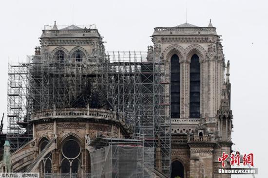 当地时间4月15日,巴黎圣母院浴火燃烧,尖塔倒塌,三分之二的屋顶被烧毁。图为经历数小时扑救后的巴黎圣母院,顶部脚手架附近明显烧成黑色。