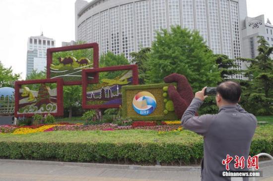 """4月18日,北京朝阳门的""""一带一路""""主题花坛吸引市民拍照。中新社记者 贾天勇 摄"""