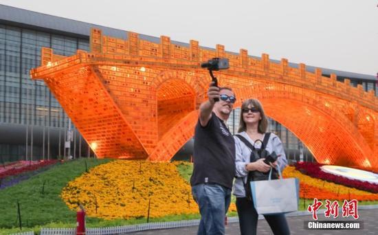 """4月18日晚,北京奥林匹克公园内的""""丝路金桥""""主题景观点亮灯光,吸引游客拍照。""""丝路金桥""""由中国艺术家舒勇创作,长28米、高6米、宽4米,是以""""一带一路""""倡议为语境的大型艺术作品,此次作为第二届""""一带一路""""国际合作高峰论坛的主题花坛亮相。中新社记者 贾天勇 摄"""