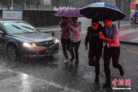 图为广州民众冒雨出行。中新社记者 陈骥F 摄