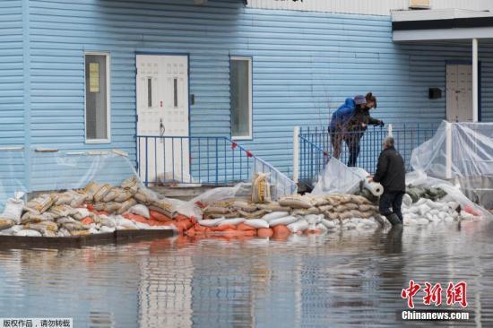 资料图:当地时间4月20日,加拿大魁北克省圣玛丽市,暴雨造成Chaudiere河河水决堤,引发洪水。图为当地民众在摆放沙袋抵御洪水。